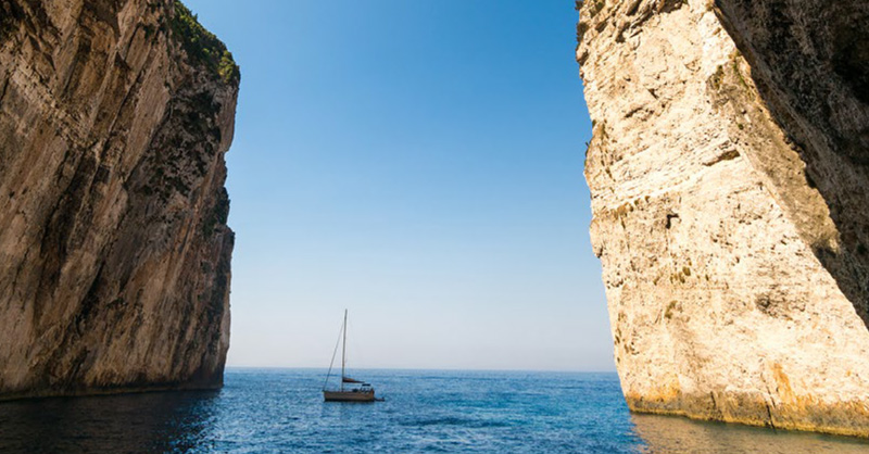 Sailboat in the middle of two large cliffs