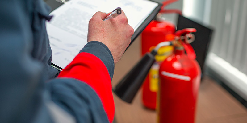 Inspecting fire safety equipment with checklist