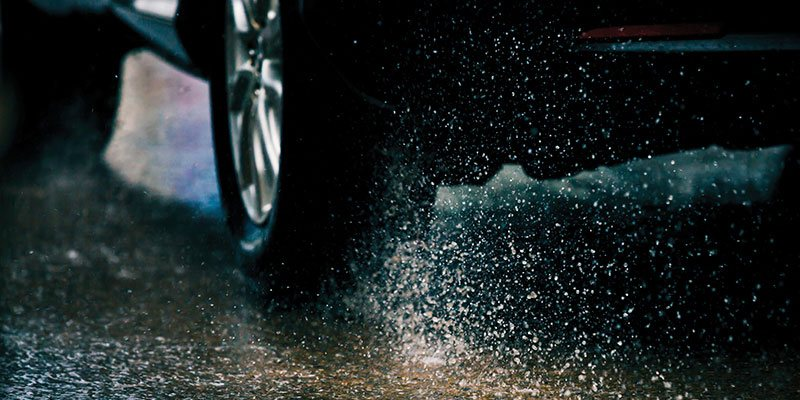 Close up of car tire skidding on wet road