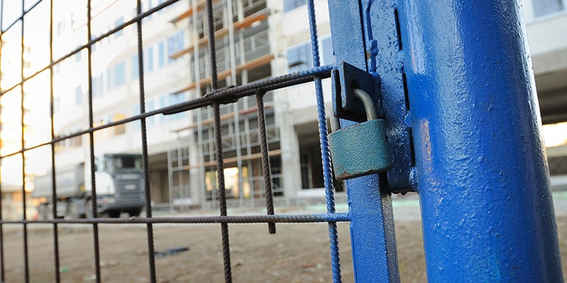 Construction site with blue gate and padlock