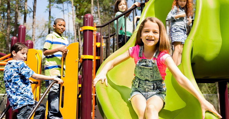 Five children playing on slide with girl smiling going down green slide