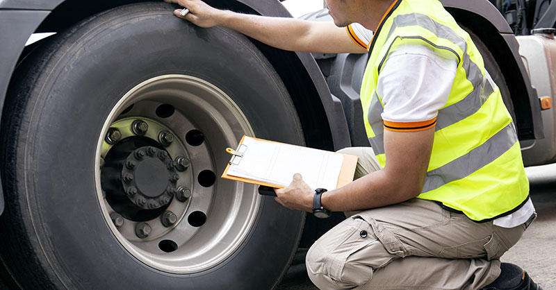 Male looking at truck tire