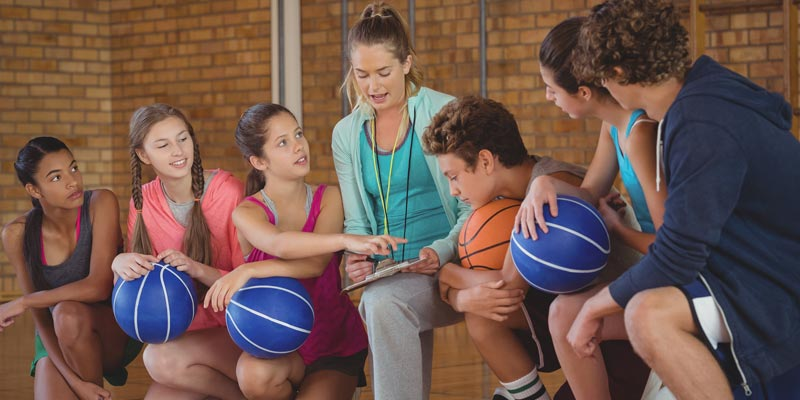 Female coach with a group of high school students in gym with basketballs