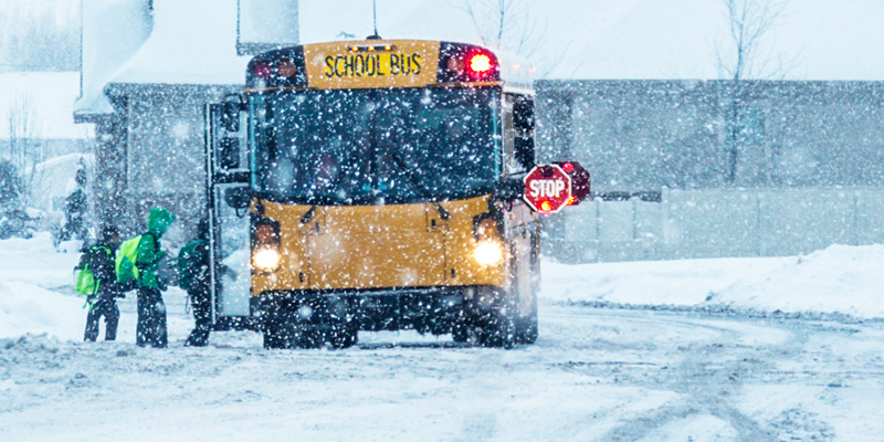 School bus picking up grade school students during a heavy snow fall