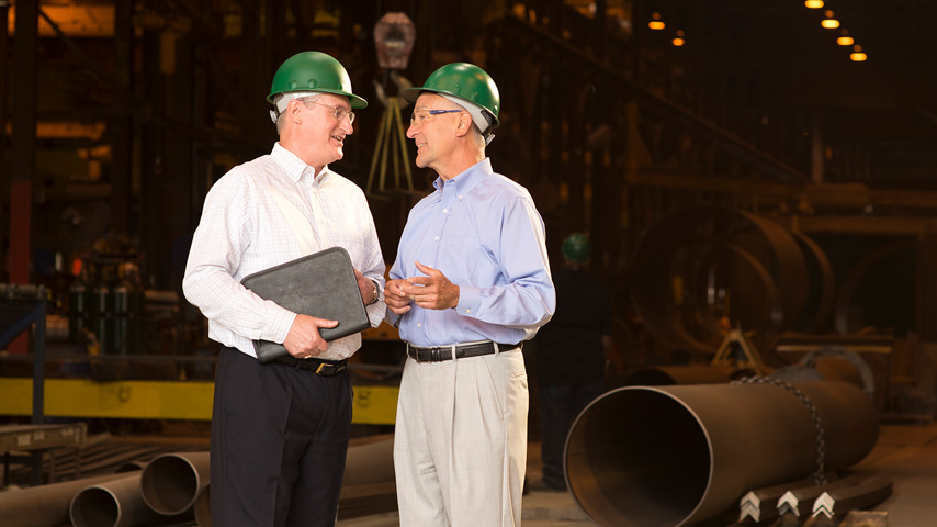 Two men wearing green hard hats in a warehouse