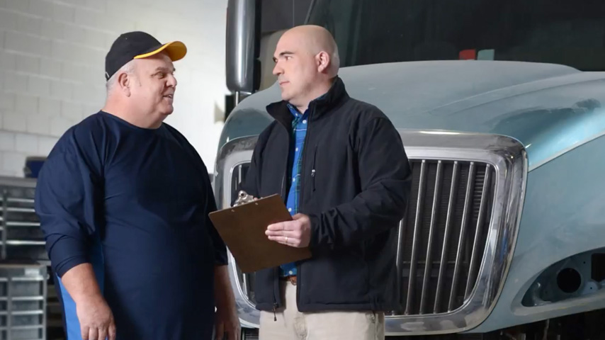 Two men talk and standing in front of a parked semi truck