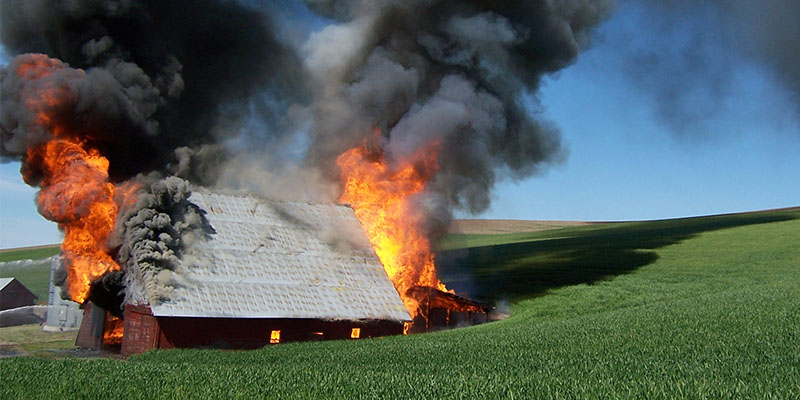 Barn on fire in a field