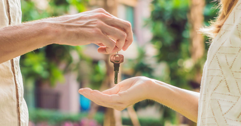 Male handing female house keys