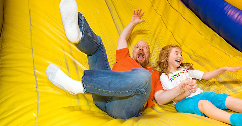 Father and daughter sliding down inflatable slide