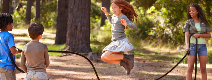 Red hair girl jumping rope with boys and girl