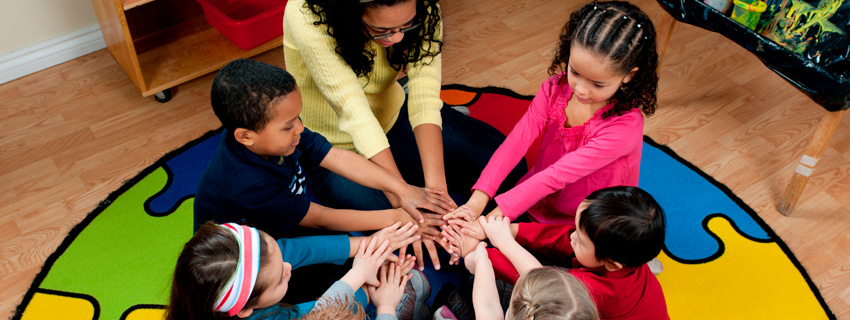 Teacher with daycare students in circle with hands together in the middle