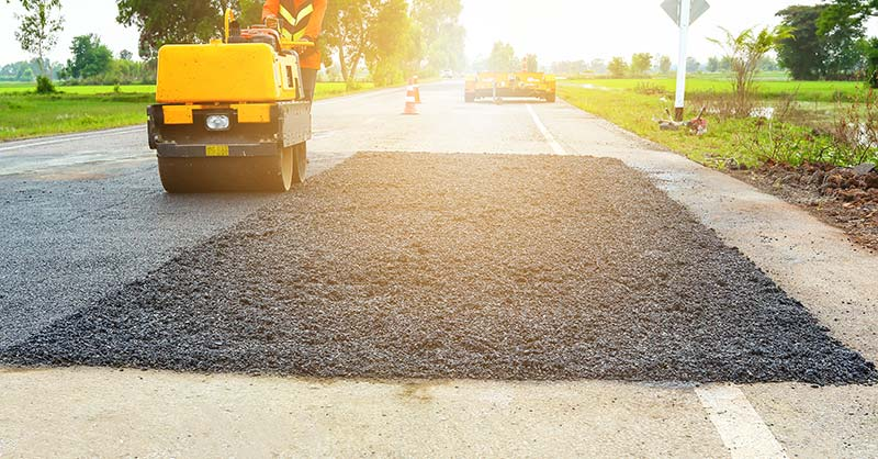 photo of asphalt roller truck next to asphalt patch on road