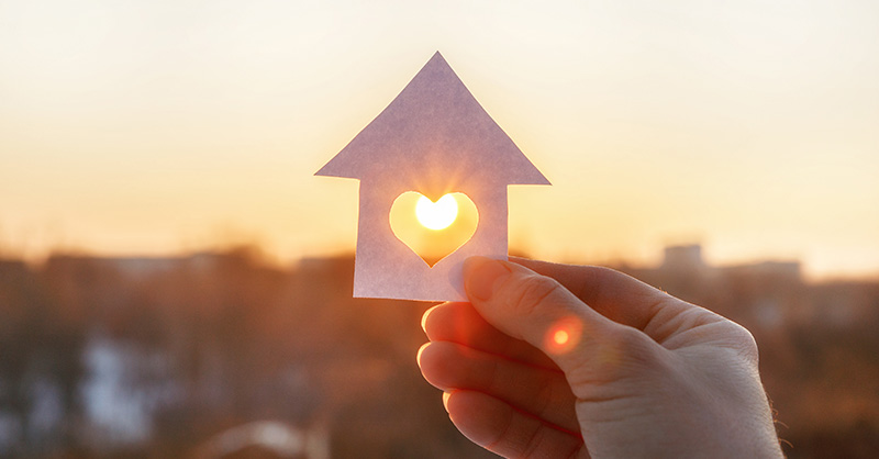 Female hand holding paper cut out of house with heart in the middle with sunset visible through heart