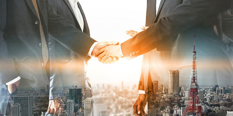businessmen shaking hands on an overlay of a cityscape