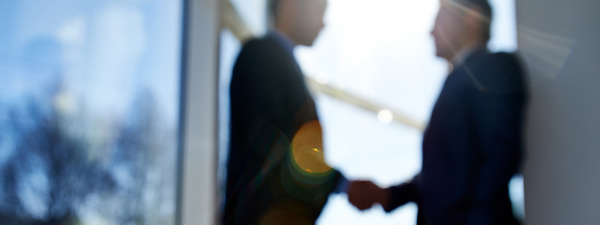 Blurry image of businessmen shaking hand in front of bright window