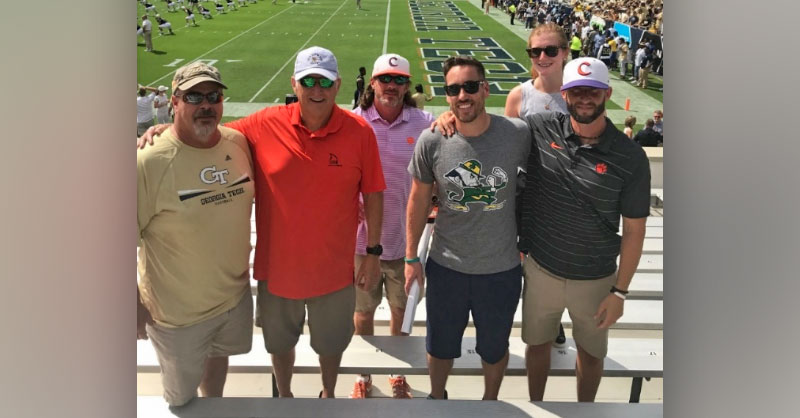 Group photo of five males and a female in the stands of a college football game