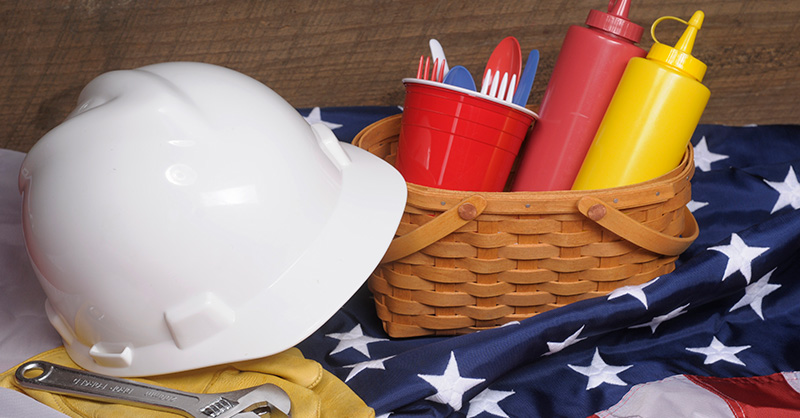 Picture of white construction hard hat with picnic basket on top of US flag filled with plastic untensils, ketchup and mustard bottles