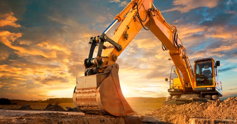 Commerical excavator on top of dirt with sunset in background