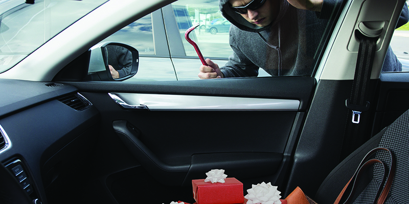 Thief with crowbar in car window looking at present in front seat