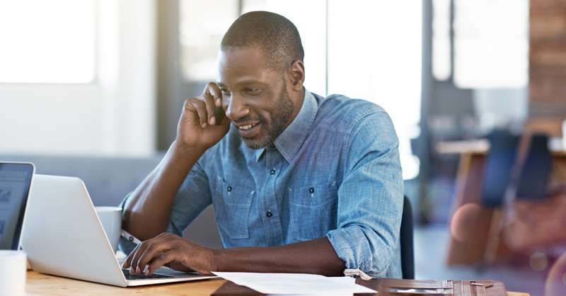 Smiling African American male on phone in front of laptop