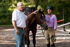 Senior man petting a horse with trainer smiling.