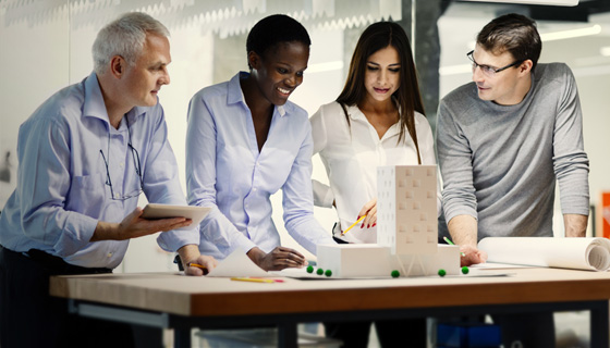 Four coworkers looking at building model on table