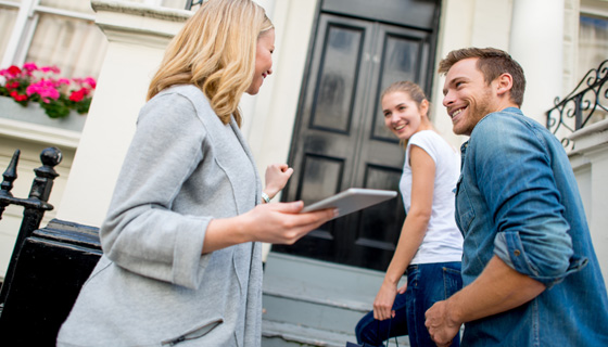 Real estate agent talking to couple as they walk in home