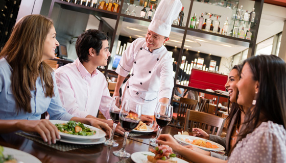 Friends being greated by chef at restaurant
